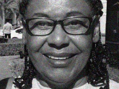 Foto de perfil de Cida Bento em preto e branco. Ela está sorrindo, usa óculos cabelos e está com os cabelos trançados